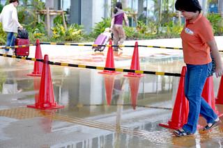 水たまりを慎重に歩く空港利用者や、水たまりを避けて歩く観光客ら=8日午後、南ぬ島石垣空港ターミナル