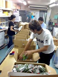 顧客に送る商品を段ボール箱に詰める人たち=6月1日(ISM提供)