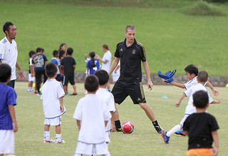 キジェルモ・エスクデロ・テジョコーチと楽しく練習する子供たち=8月31日、サッカーパークあかんま