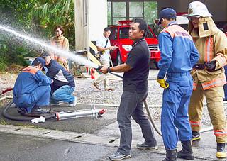 防災教室で消火作業を体験する参加者=1日午後、石垣消防本部川平出張所