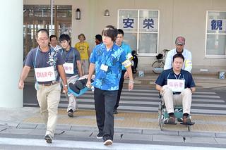 傷病者を担架に乗せ、指定避難ビルに向かう石垣港離島ターミナル入居者ら=4日午前、同ターミナル前