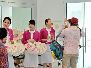 記念品を贈り、笑顔で搭乗客を送り出す客室乗務員ら=13日午前10時ごろ