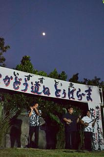 月明かりの下で思い思いにとぅばらーまを歌い上げた出演者ら=16日夜、平得のとぅばらーま歌碑前広場