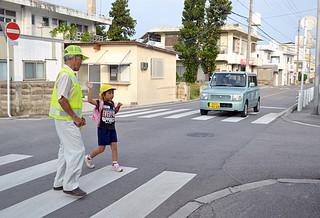 小学校の登校時間、ボランティアが子どもたちの安全を確保する=5日午前7時50分ごろ登野城校区の通称4号線