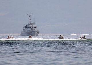捜索を行う海保と消防の潜水士=9日午前10時40分ごろ、米原海岸沖合