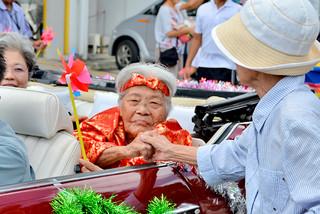 長寿を祝う住民と握手をする前盛キクさん=13日午前、真栄里地区