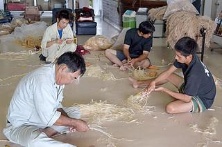 先輩からの指導を受け、獅子の修繕作業を行う地域の青年たち=13日午前、平得公民館