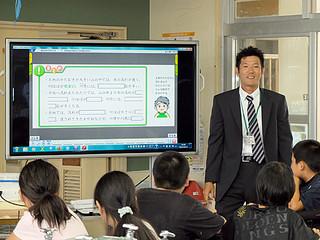 手始めに石垣小学校に導入された電子黒板。呉屋正樹教諭(右)がさっそく理科の授業で使った=15日午後2時すぎ、理科室
