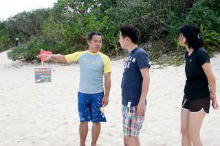 離岸流の危険性を説明する花城康志さん 左は独自に制作した看板=15日午前、石垣市米原ビーチ