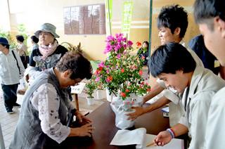 緑地土木科の生徒が育てた花を、市民が買う様子=18日午後、八重山農林高校事務室前ピロティ