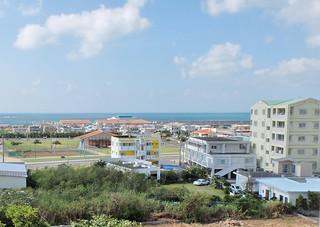 海に面し、津波時の避難が課題となっていた八島小学校(奥の赤瓦屋根)。コンフォート真栄里(右端)が津波避難ビルとして使用できるようになった=30日午前10時半ごろ