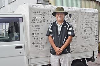 各地での寄せ書きが書かれた軽トラとともに日本縦断を終えた仲本さん=1日午前、本社駐車場
