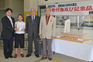 母校の登野城小学校に50万円とサバニ帆船の模型を贈った「記念品を贈る会」の松本淳代表(右)と製作した青山武次さん(その左)=3日午後、同校