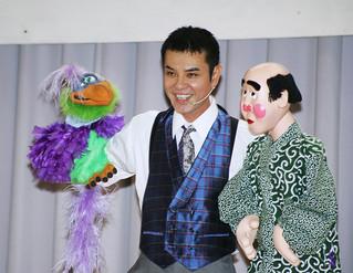 「サトル」(鳥)とカルロスの人形を使い腹話術を披露するいっこく堂=5日午前、名蔵小中学校体育館