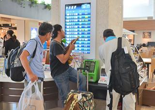 携帯電話が使えないため、公衆電話を利用した観光客ら=8日午後、南ぬ島石垣空港