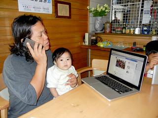 石垣市内に住む友人のフィリピン人と電話をしながら、郷里の様子をインターネットで見る上原マリベルさん=14日午前、石垣市登野城の自宅