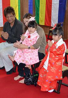 七五三で参拝し、おはらいの後に手を合わせる川満洋和、由希乃さんと娘の琉央ちゃん、結愛ちゃん(左から)=15日午後、桃林寺