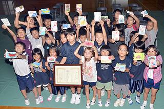 第10回手づくり絵はがきコンクールで最優秀賞を受賞した竹富小の児童ら=15日午後、同校体育館学校