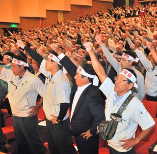 サトウキビ生産振興対策の充実強化を求める大会宣言を採択し、ガンバロー三唱した県内のサトウキビ生産者ら=20日午後、豊見城市