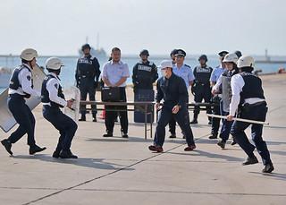 2013年度石垣港保安対策総合訓練でクルーズ船から下船したテロリスト役の男性を取り押さえる警察官=27日午後、石垣港浜崎地区国際埠頭