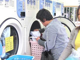 降り続く雨で洗濯物が乾かず、コインランドリーを利用する人々=12日午後5時ごろ、真栄里