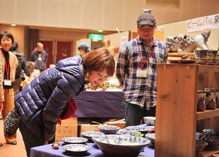 第4回やきもの祭りで各工房の独特な作品を熱心に見入る参観者=27日午後、石垣市民会館中ホール