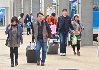 年末年始を沖縄本島や本土で過ごすため、到着したバスからチェックインカウンターに向かう旅行客ら=30日午後、南ぬ島石垣空港