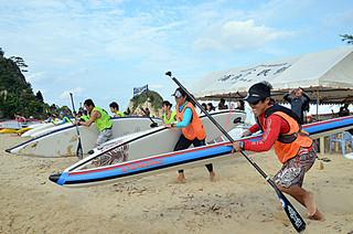 スタート=浜辺でボードを持ち、一斉にスタートを切った郡内初開催となる西表SUPフェスティバル2013
