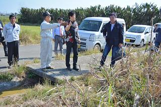 実証実験が行われる池原さんの畑を確認する関係者ら=8日午後、市内新川