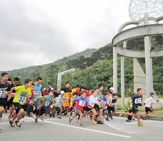 強風のなか、一斉にスタートする第13回西表島子午線マラソンの出場者=13日午後、西表子午線ふれあい館前