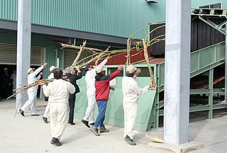 圧搾機にサトウキビを投入して操業の安全祈願する西村社長ら関係者=18日、波照間製糖