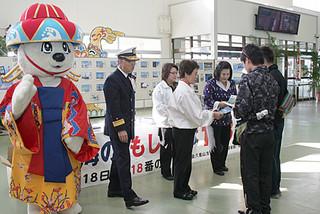 「118番の日」にちなみ観光客らに118番の正しい利用を呼びかける海保関係者ら=18日午前、石垣港離島ターミナル