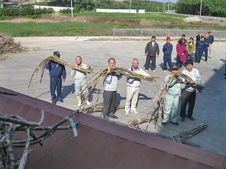 竹富町小浜製糖工場の今期操業開始にあたり原料のサトウキビをコンベアに投入するJA八重山地区本部の山田本部長(中央)ら=16日午後、同製糖工場