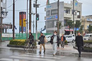 厚手の上着を着込み、寒そうに歩く人たち=21日午後、730交差点
