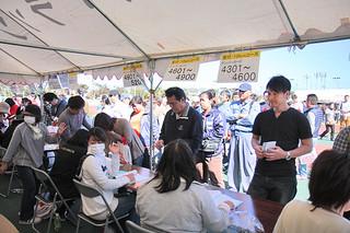 石垣島マラソンのナンバーカードを受け取った出場者=25日午後、市中央運動公園陸上競技場