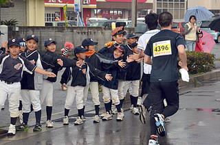 選手に声援を送りながらハイタッチを交わす少年オリオンズのメンバーら=26日午後、ベスト電器石垣店前