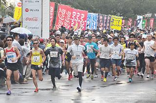 第12回石垣島マラソンで号砲を合図に一斉にゲートから飛び出すフルと23㌔の参加者ら=26日午前、石垣市中央運動公園陸上競技場