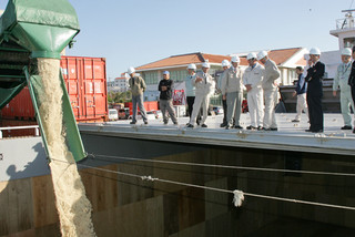 初荷の粗糖を砂糖運搬船「栄球丸」に積み込むのを見守る関係者ら=28日午前、石垣港