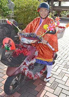 カジマヤーの衣装を着てミニバイクにまたがる下里さん=1月31日午後、市民会館前