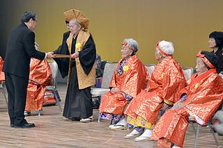 生年祝頌状および記念品贈呈式で漢那副市長から頌状が贈呈された97歳のカジマヤーを迎えた生年者=1月31日午後、市民会館大ホール