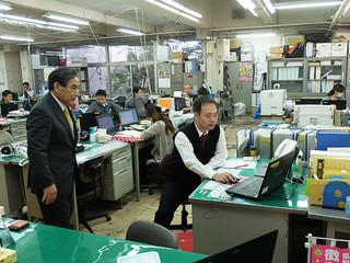 漢那副市長(左)に義務履行証明書のワンストップ化を実演し、説明する担当職員=3日午前、市役所納税課