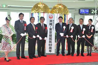 くす玉を割り沖縄-東京線就航60周年の節目を祝う日本航空の植木義晴社長(右から4人目)と関係者=5日、那覇空港国内線