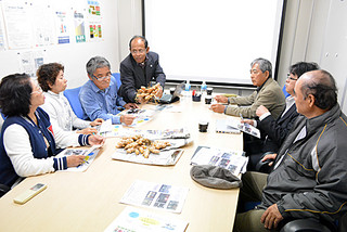 説明会で新品種の琉大ゴールドを手に説明するモハメド准教授(中央)=6日午後、経営企画会議