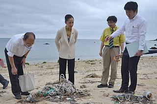 環境省や県、市の担当者から漂着物について説明を受けた浮島智子政務官(中)=7日午後、伊野田海岸