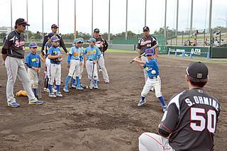 伊志嶺翔大(左)や井上晴哉(右)からバッティングの指導を受ける子どもたち=8日午後、市中央運動公園野球場
