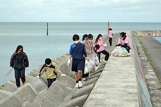 消波ブロックに捨てられたごみを拾う八重山商工高校観光コースの生徒たち=8日午前、八島小南側の防波堤周辺