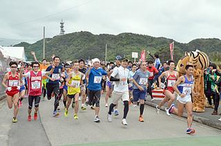 第21回やまねこマラソン大会で西表島の雄大な自然をバックにスタートを切る参加者=8日午後、上原小学校校門前