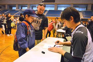 マリーンズ選手サイン会で涌井秀章投手からサインをもらう参加者=9日午後、石垣市総合体育館