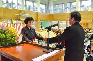 吉原小学校の創立60周年記念式典で、榮多喜仁校長(右)から感謝状を受け取る歴代校長ら=9日午前、同校体育館