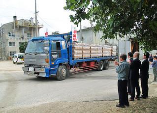 与那国製糖工場の出荷式。関係者に囲まれながら黒糖を満載したトラックが工場を出発した=18日、与那国製糖工場